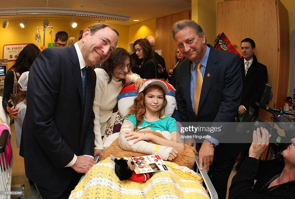 Commissioner Gary Bettman (L) and Owner, governor and chairman Eugene Melnyk of the Ottawa Senators visits with a young patient at the unveiling of the NHL All-Star Legacy Playroom at Children's Hospital of Eastern Ontario on January 27, 2012 in Ottawa, Canada.
