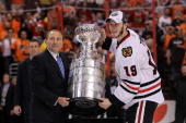 Commissioner Gary Bettman presents Jonathan Toews of the Chicago Blackhawks with the Stanley Cup after teammate Patrick Kane scored the gamewinning...