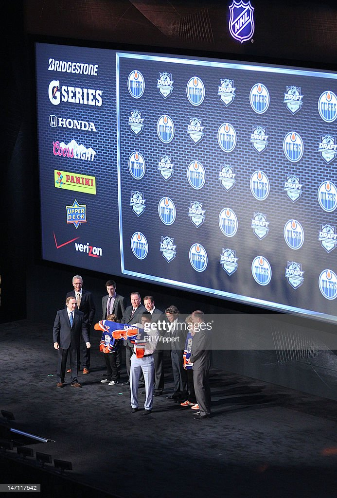 NHL Commissioner Gary Bettman, Senior VP of Hockey Operations Craig MacTavish, 2011 First overall pick Ryan Nugent-Hopkins, Head Amateur Scout Stu MacGregor, General Manager Steve Tambellini, Oilers Governor/Owner Daryl Katz and President of Hockey Operations Kevin Lowe look on as first overall pick Nail Yakupov puts on his jersey during Round One of the 2012 NHL Entry Draft at Consol Energy Center on June 22, 2012 in Pittsburgh, Pennsylvania.