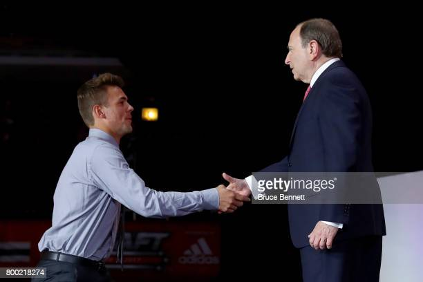Commissioner Gary Bettman shakes hands with Ryan Poehling after being selected 25th overall by the Montreal Canadiens during the 2017 NHL Draft at...