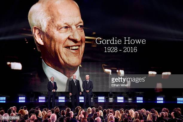 Commissioner Gary Bettman stands with Mark Howe and Marty Howe as they speak during the In Memoriam portion of the show as a picture of their father...
