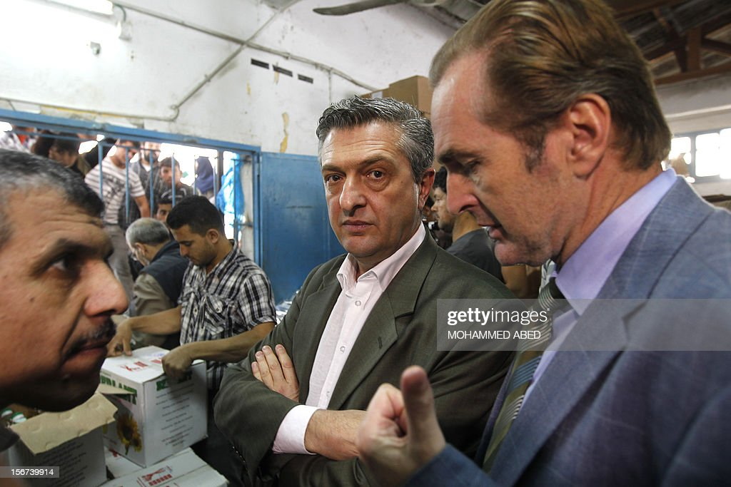 Commissioner General of the UN Relief and Works Agency (UNRWA), Filippo Grandi (C) listens on during a visit to a supplies center after it was damaged in an Israeli airstrike directed at the nearby Hamas police headquarters at the Jabalya refugee camp, in the northern Gaza Strip on November 20, 2012. Israel halted a threatened Gaza ground offensive to give Egyptian-led truce talks a chance as top diplomats flew in to boost efforts to end nearly a week of cross-border violence. AFP PHOTO/MOHAMMED ABED