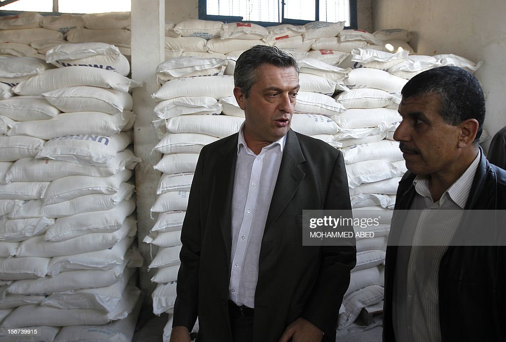 Commissioner General of the UN Relief and Works Agency (UNRWA), Filippo Grandi (L) listens on during a visit to a UN supplies center after it was damaged in an Israeli airstrike directed at the nearby Hamas police headquarters at the Jabalya refugee camp, in the northern Gaza Strip on November 20, 2012. Israel halted a threatened Gaza ground offensive to give Egyptian-led truce talks a chance as top diplomats flew in to boost efforts to end nearly a week of cross-border violence. AFP PHOTO/MOHAMMED ABED