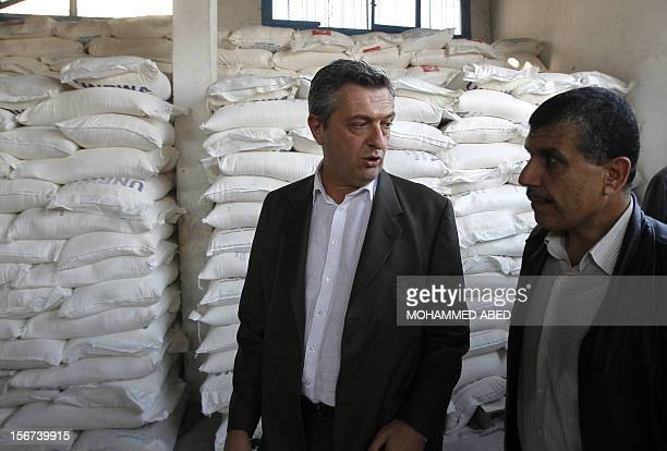 Commissioner General of the UN Relief and Works Agency Filippo Grandi listens on during a visit to a UN supplies center after it was damaged in an...