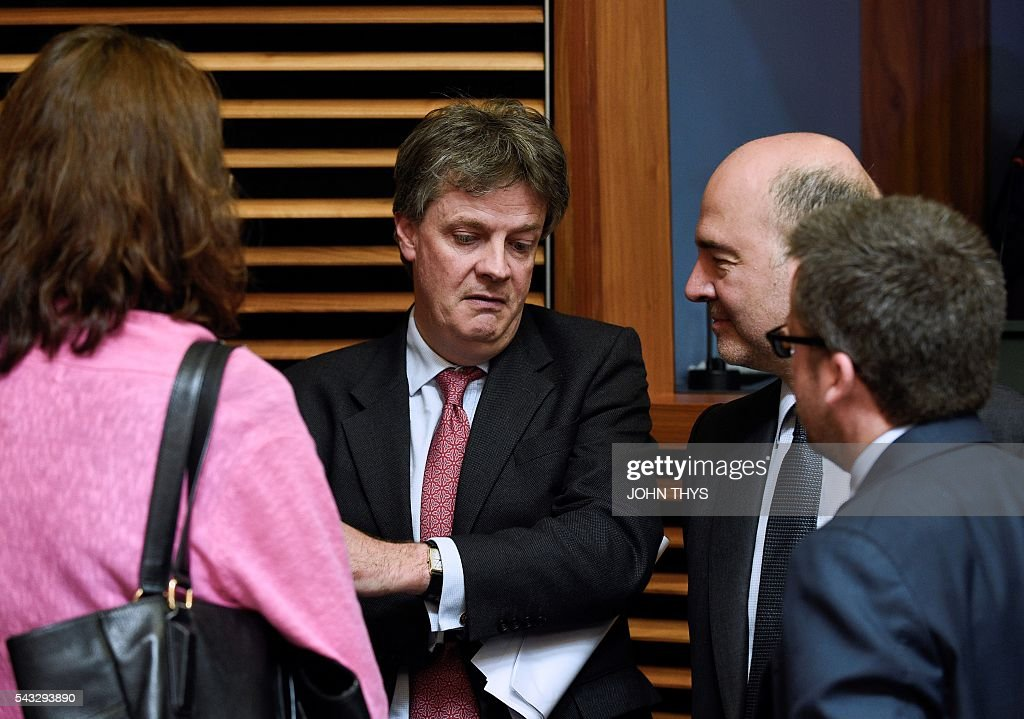 EU Commissioner of Financial Stability, Financial Services and Capital Markets Union Jonathan Hill (C) talks with EU Commissioner of Economic an d Financial Affairs, Taxation and Customs Pierre Moscovici (R) during a Commissioners college meeting at the EU headquarters in Brussels on June 27, 2016. In an early sign of the Brexit fallout in Brussels, Britain's European commissioner for financial services, Jonathan Hill, said he would stand down. / AFP / JOHN