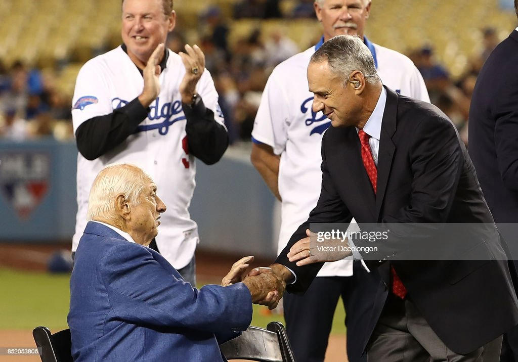Commissioner Rob Manfred shakes the hand of former Los Angeles Dodgers manager Tommy Lasorda during a pre-game ceremony to pay tribute to Lasorda on his 90th birthday prior to the MLB game between the San Francisco Giants and the Los Angeles Dodgers at Dodger Stadium on September 22, 2017 in Los Angeles, California.