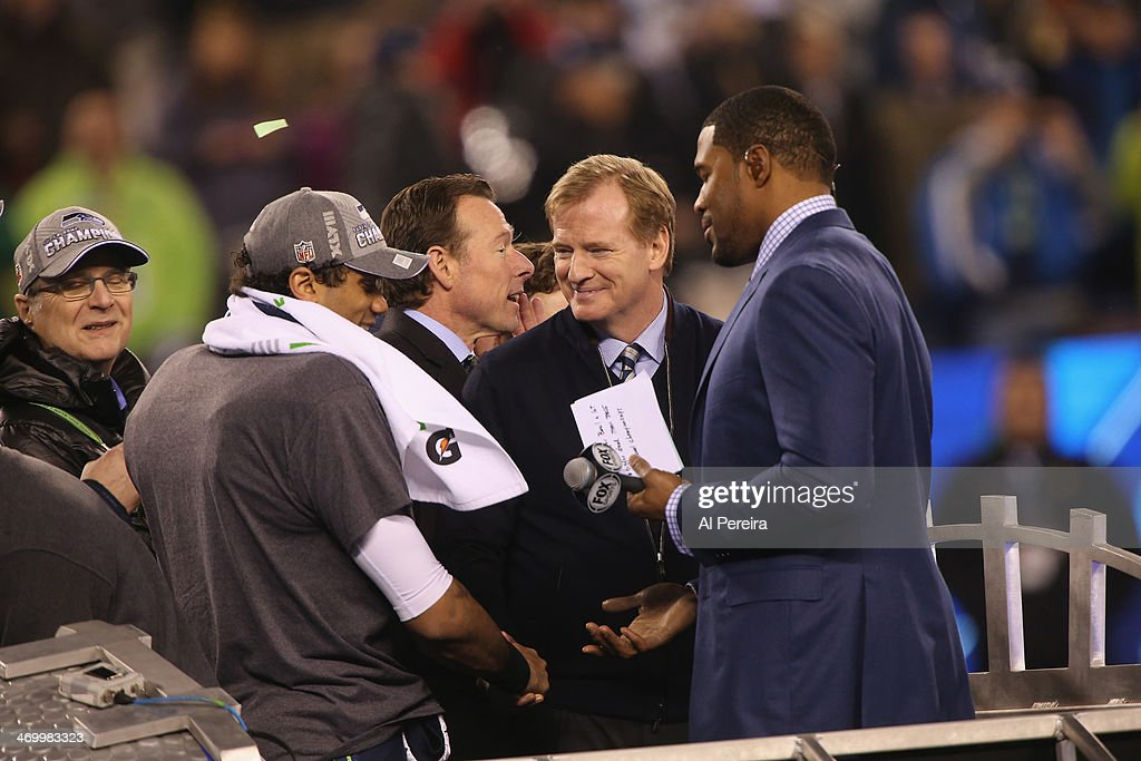 Commissioner Roger Goodell congratulates Quarterback Russell Wilson #3 of the Seattle Seahawks as team owner Paul Allen and Postgame show Host Michael Strahan look on after the game against the Denver Broncos in Super Bowl XLVIII at MetLife Stadium on February 2, 2014 in East Rutherford, New Jersey.