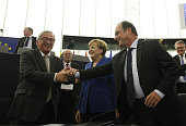 EU Commission's President JeanClaude Juncker welcomes Germany's Chancellor Angela Merkel and French president Francois Hollande ahead of their joint...