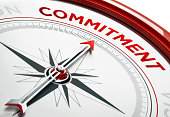 Arrow of a compass is pointing commitment text on the compass. Arrow , commitment text and the frame of compass are metallic red in color. White background. Horizontal composition with copy space. Com