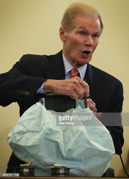 Committee Chairman Sen Bill Nelson holds up a shrapnel demaged airbag that was manufactured by Takata during a hearing before the Senate Commerce...