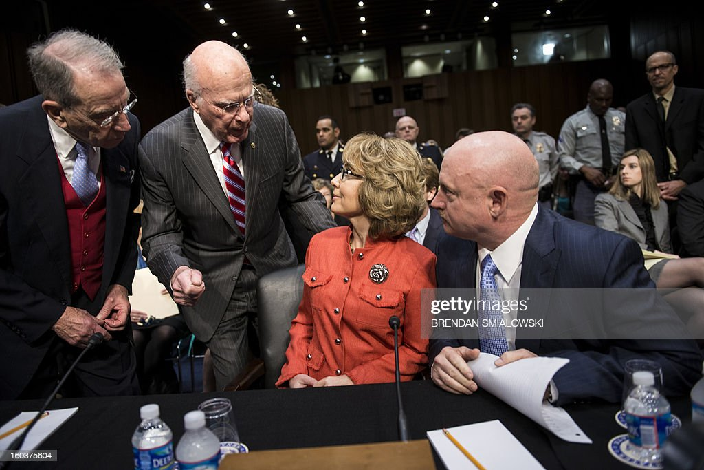 Committee ranking member Senator Chuck Grassley(L) ,R-IA, and chairman Senator Patrick Leahy (2L),D-VT, talk to shooting victim former Arizona Rep. Gabrielle Giffords (2R) and her husband retired Astronaut Mark Kelly, before a hearing of the Senate Judiciary Committee on Capitol Hill January 30, 2013 in Washington, DC. The committee held the hearing with retired Astronaut Mark Kelly, husband of former Rep. Gabrielle Giffords, Wayne LaPierre, Chief Executive Officer of the National Rifle Association, and others to testify about solutions to gun violence in the United States. AFP PHOTO/Brendan SMIALOWSKI