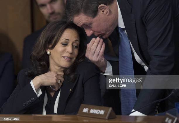 Committee Ranking Member US Senator Mark Warner Democrat of Virginia speaks with US Senator Kamala Harris Democrat of California during a Senate...