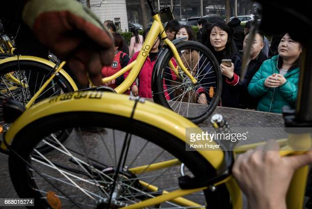 Commmuters waiter as workers from the bike share company Ofo unload new bike shares at a metro station during rush hour on March 30 2017 in Beijing...