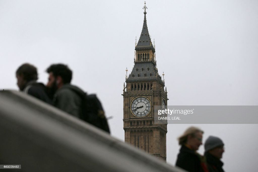 Commmuters walk near The Elizabeth Tower, better known as 'Big Ben', and the Houses of Parliament in central London on March 14, 2017. Prime Minister Theresa May is set to begin the countdown to Brexit after parliament gave her the green light -- and Scotland wrong-footed her by launching a fresh bid for independence. Downing Street has played down speculation that May could announce Tuesday that she is triggering the Article 50 process to leave the European Union, indicating that it would take place later in the month. / AFP PHOTO / Daniel LEAL