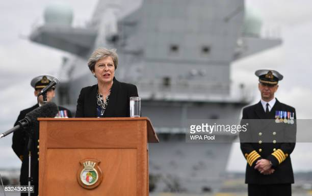Commodore Jerry Kyd listens as Britain's Prime Minister Theresa May stands on the flight deck and speaks to crew members of the 65000tonne British...