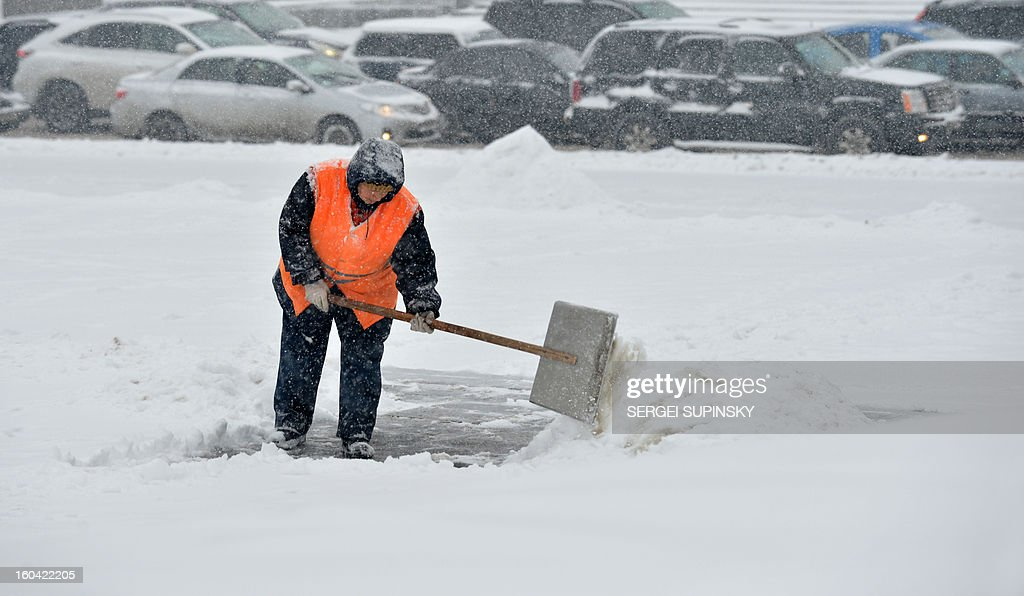 A communal worker cleans a road during a heavy snow fall in Kiev on January 31, 2013.