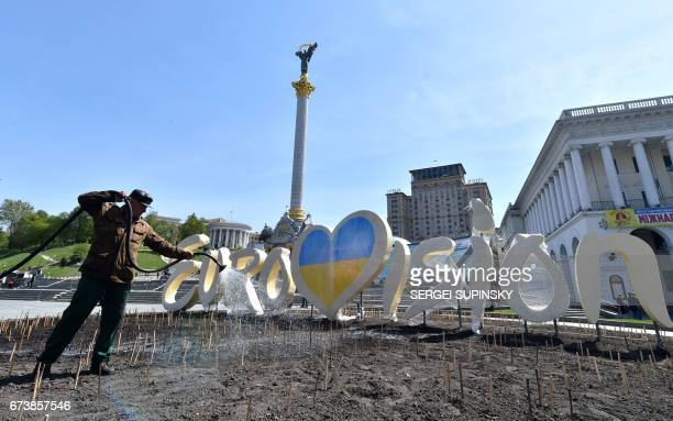 A communal worker hoses a flowered bed at a decorative signing depicting the official logo of Eurovision Song Contest 2017 during the preparations at...