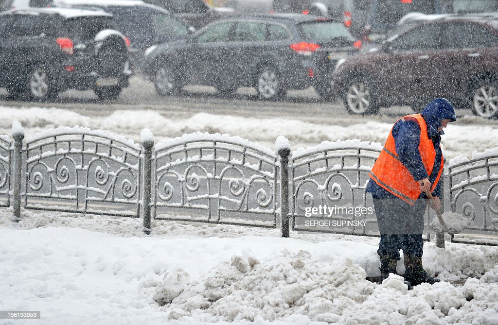 A communal worker removes snow with a shovel during a heavy snowfall in Kiev on December 11, 2012. AFP PHOTO/ SERGEI SUPINSKY
