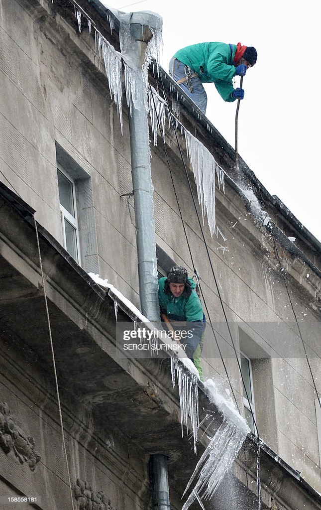 Communal workers clean a roof from snow and icicles on a frosty winter day in the Ukrainian capital Kiev on December 19, 2012.
