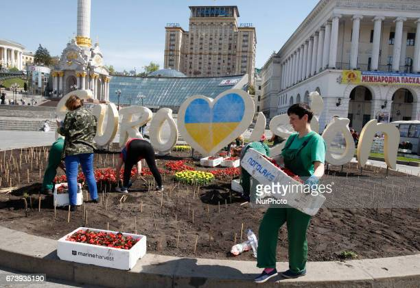 Communal workers plant flowers in front of a decorative the Eurovision Song Contest 2017 logo during the preparations on Independence Square in Kiev...