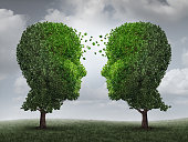 Communication and growth concept as a growing partnership and teamwork exchange in business with two trees in the shape of human heads on a sky with leaves exchanging from one face to the other as a c