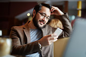 Bearded man in eyeglasses reading sms in smartphone while sitting in cafe