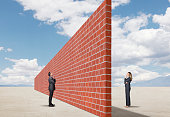 A businessman and a businesswoman stand on opposite sides of a tall and long brick wall that stands in an open and remote desert scene.  They are both wondering how they will overcome the barrier in c