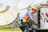 Communications engineer getting equipment from truck with satellite antenna in background