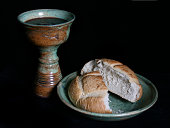 Communion elements in the chalice and paten; bread and wine grape juice on the plate and cup.
