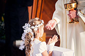 Communion and clergyman. Priest holds Holy Communion in his hands. Priest gives the Body of Christ during the First Holy Communion