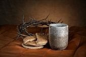 Communion cup and bread with crown of thorns in background
