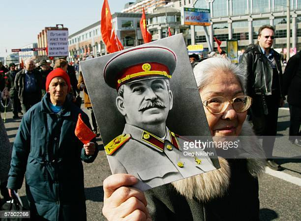 Communist demonstrator holds up a portrait of soviet dictator Joseph Stalin as she marches during a May Day rally May 1 2006 in central Moscow Russia...
