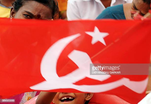 A Communist flag flutters as Indian opposition and left activists demonstrate against the price hike of essential commodities during a protest rally...
