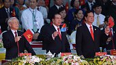 Communist Party Chief Nguyen Phu Trong former Communist Party Chief Nong Duc Manh and Prime Minister Nguyen Tan Dung wave flags while watching a...