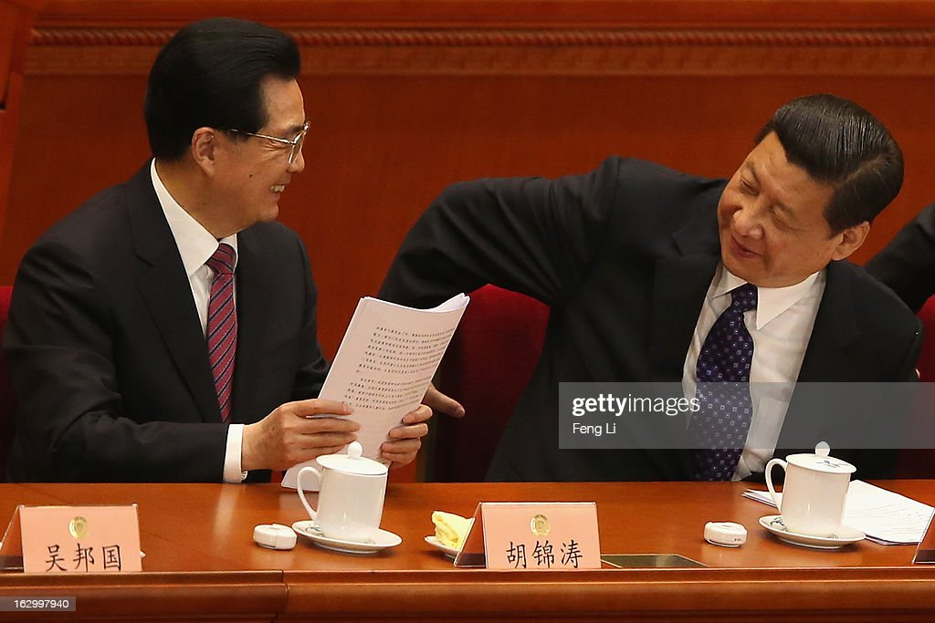 Communist Party chief Xi Jinping and Chinese President Hu Jintao look at each other as they leave after the opening session of the Chinese People's...
