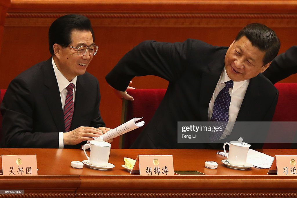 Communist Party chief Xi Jinping and Chinese President Hu Jintao leave after the opening session of the Chinese People's Political Consultative...