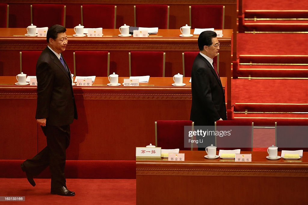Communist Party chief Xi Jinping (L) walks behind Chinese President Hu Jintao (R) at the opening session of the annual National People's Congress in Beijing's Great Hall of the People on March 5, 2013 in Beijing, China. Chinese Premier Wen Jiabao stressed Tuesday that the government should adopt effective measures to prevent and control pollution in response to people's expectations of having a good living environment.