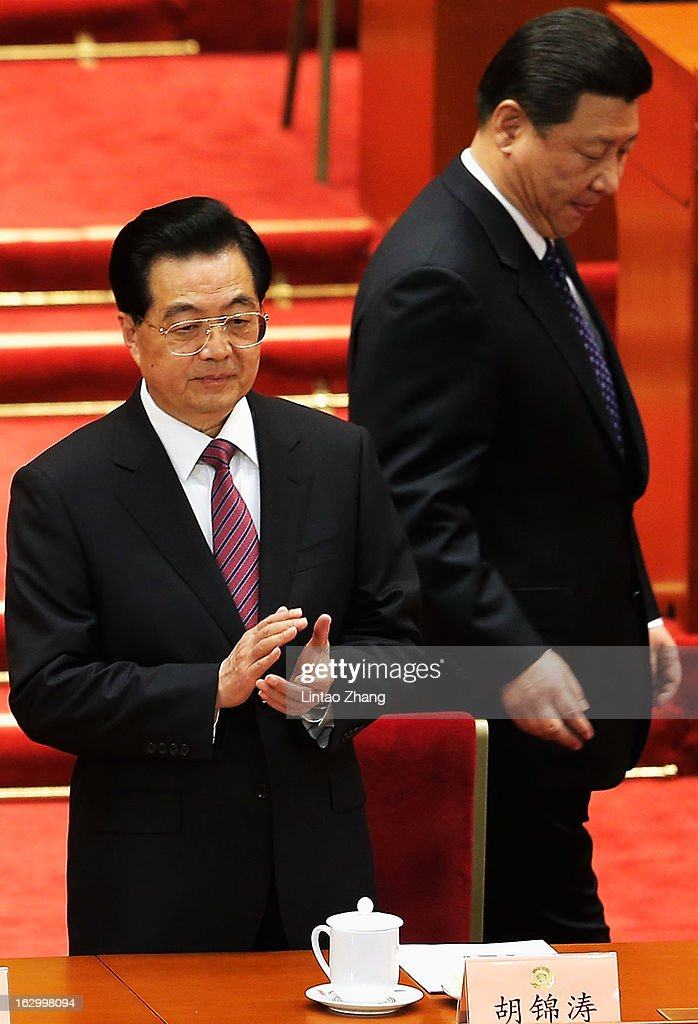 Communist Party chief Xi Jinping walks past Chinese President Hu Jintao before the opening session of the Chinese People's Political Consultative...