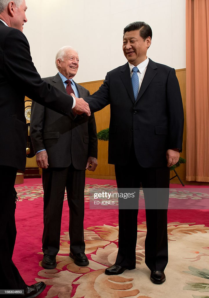 Communist Party leader Xi Jinping (R) shakes hands with an unidentified guest (L) as he stands beside former US president Jimmy Carter (C) in room 202 of the Zhongnanhai leadership compound in Beijing on December 13, 2012. Carter congratulated Xi on his new position before the pair sat down for talks. AFP PHOTO / POOL / Ed Jones
