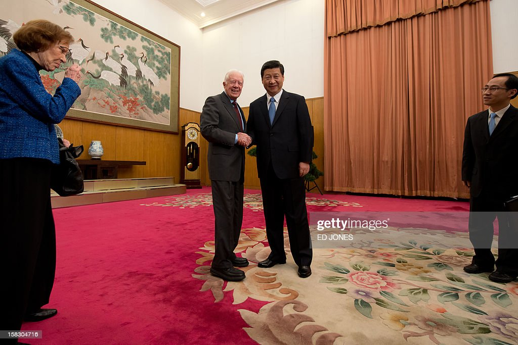 Communist Party leader Xi Jinping (2nd R) shakes hands with former US president Jimmy Carter (2nd L) as his wife Rosilyn (L) stands by, in room 202 of the Zhongnanhai leadership compound in Beijing on December 13, 2012. Carter congratulated Xi on his new position before the pair sat down for talks. AFP PHOTO / POOL / Ed Jones