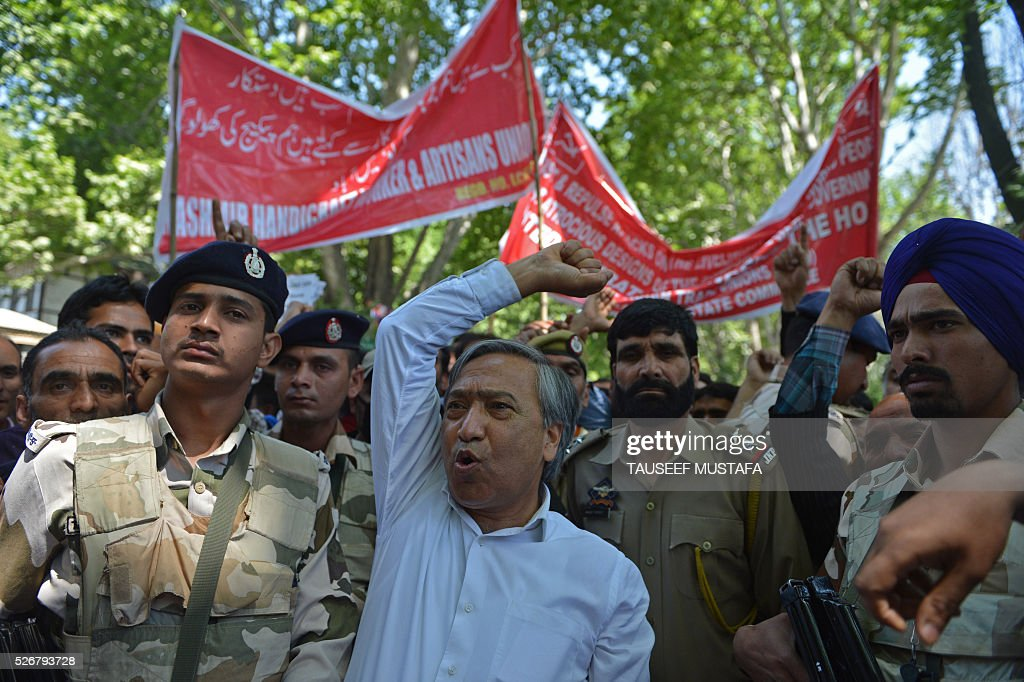 Communist Party of India (Marxist)(CPI-M)leader M.Y.Tarigami(C) is watched by security personnel as he shouts slogans while contractual and daily wage employees of the state government take part in a protest for better pay and job security as they take part in a rally in Srinagar on May 1, 2016. Workers from various labour groups took to the streets on the occasion of the International Labour Day which is observed worldwide. / AFP / TAUSEEF