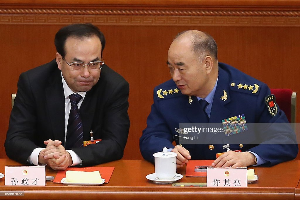 Communist Party Secretary of Chongqing Sun Zhengcai (L) talks with Chinese vice chairman of the Central Military Commission Xu Qiliang (R) during the fourth plenary meeting of the National People's Congress (NPC) at the Great Hall of the People on March 14, 2013 in Beijing, China. Xi Jinping, general secretary of the Communist Party of China Central Committee, was elected President of the People's Republic of China and Chairman of the Central Military Commission on Thursday.