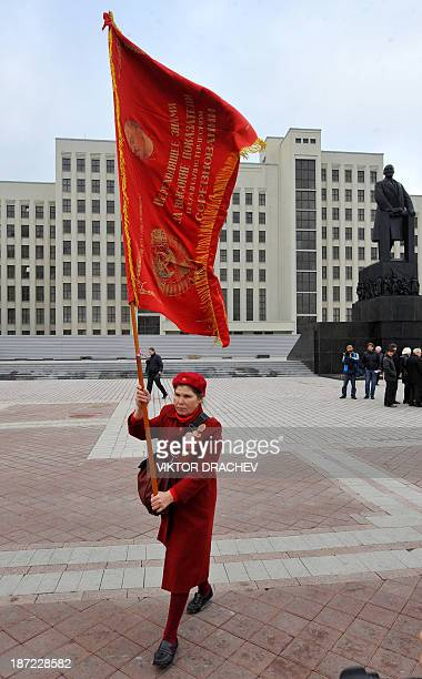 A communist party supporter carries a red flag near a monument to the Soviet Union founder Vladimir Lenin in central Minsk on November 7 during her...