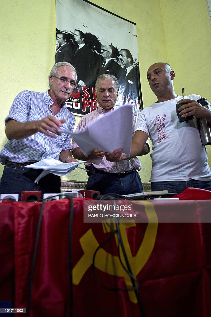 Communist Party's general secretary Eduardo Lorier, Uruguay's Minister of Health, Chilean-born Jorge Venegas, and Marcelo Abdala, health union leader, read a document before a a press conference at the Uruguayan Communist Party's headquarters in Montevideo on February 14, 2013. The Communist Party will ask Uruguay's President Jose Mujica to remove Venegas, after accusations were presented against him for failure to comply with the law regarding foreigners in ministerial positions, and nominated Susana Muniz to replace him. AFP PHOTO/Pablo PORCIUNCULA