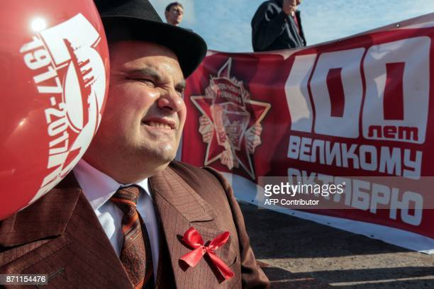 A Communist supporter holding a red balloon attends a rally in Simferopol's Lenin Square on November 7 to celebrate the 100th anniversary of The...