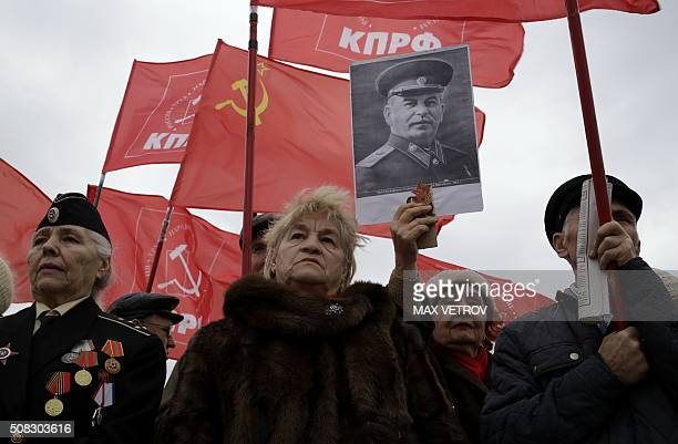 TOPSHOT Communist supporters hold red flags and a portrait of Joseph Stalin as they take part in a rally to protest against price hikes and rising...