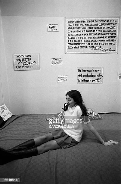 Communities In California EtatsUnis Californie janvier 1971 ici dans un magasin une femme est assise les jambes allongée sur un 'lit à eau' recouvert...