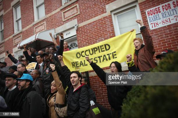 Community activists and over two hundred members of the Occupy Wall Street movement rally around a forclosed home during a march in the impoverished...