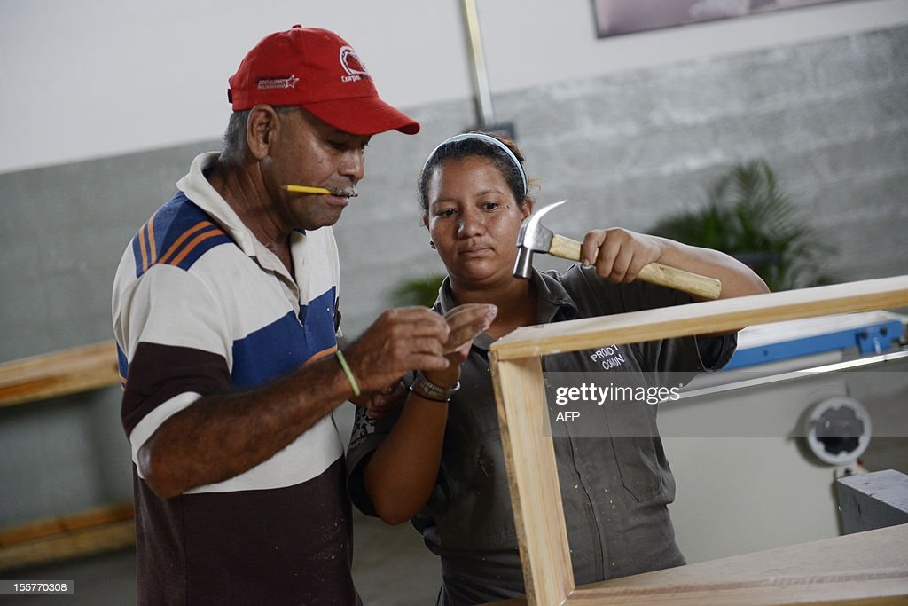 A community council member learns carpentry to apply her skills in her own community, in Valles del Tuy, Venezuela, on November 2, 2012. Promoted on a daily basis by President Hugo Chavez and his ministers, the communal socialist State is the irreversible course undertaken since the triumph of Chavez in the last presidential election. The goal is to link the whole of the population to a communal counsil by 2009, when two thirds of the Venezuelans will be organized into 'socialist communal systems'. AFP PHOTO/Leo RAMIREZ
