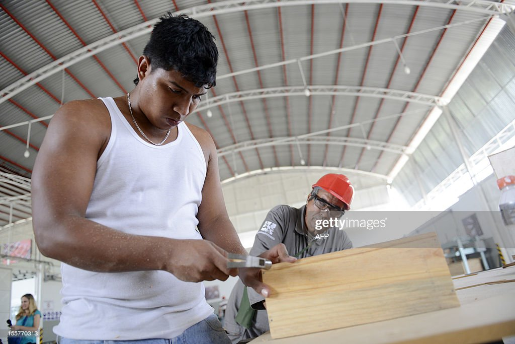 A community council member learns carpentry to apply his skills in his own community, in Valles del Tuy, Venezuela, on November 2, 2012. Promoted on a daily basis by President Hugo Chavez and his ministers, the communal socialist State is the irreversible course undertaken since the triumph of Chavez in the last presidential election. The goal is to link the whole of the population to a communal counsil by 2009, when two thirds of the Venezuelans will be organized into 'socialist communal systems'. AFP PHOTO/Leo RAMIREZ